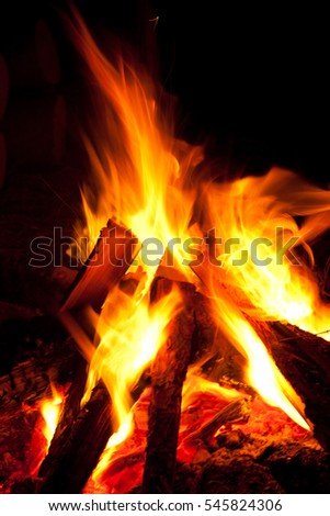 Closeup of burning red fire wood on black background