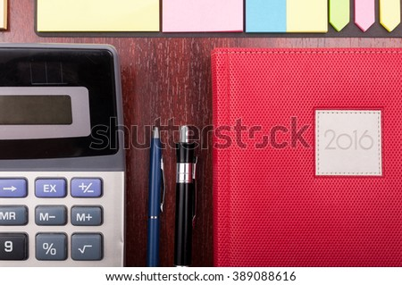 Closeup of business diary, calculator and office supplies on organized wooden desk - stock photo
