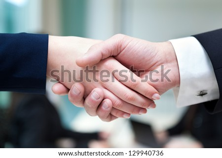 Closeup of business handshake after signing new contract at the office
