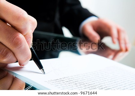 Closeup of business lady's hand with pen signing a contract on the background of her other hand touching the table