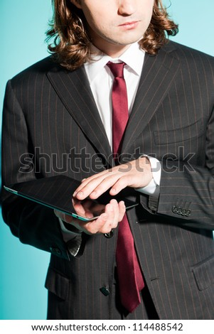 Closeup of business man with tablet. Wearing black striped suit with dark red tie. Long brown hair. Isolated on light blue background. Studio shot.
