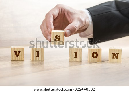 Closeup of business manager assembling a word Vision with six wooden cubes. Conceptual of business innovation and start up. - stock photo
