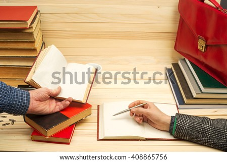 Closeup of business partners hand pointing where to sign a contract, legal papers or application form. Business meteeng.  On a wooden table books, documents, calculator, red briefcase. Copy space. - stock photo