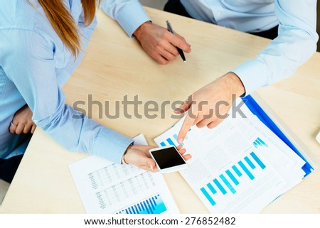 Closeup of business people talking over smartphone - stock photo