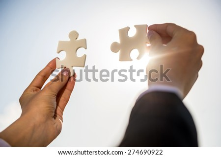 Closeup of business people wanting to put two pieces of puzzle together. - stock photo