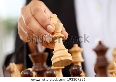 Closeup of business woman hand holding chess king piece  - stock photo