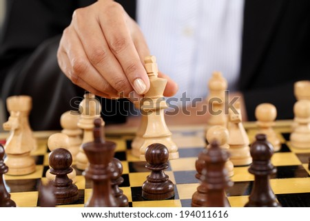 Closeup of business woman hand holding chess king piece