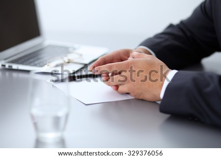 Closeup of  businessman giving a business card, sitting at the table