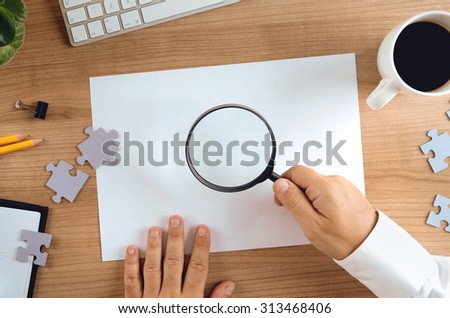 Closeup of businessman hand holding magnifier over blank paper copy space and puzzle pieces scattered on the table. Concept for website banner, mockup, presentation template and marketing materials. - stock photo