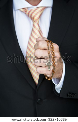 closeup of businessman holding a rosary and praying - stock photo