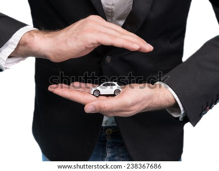 Closeup of businessman in black suit holding small car model
