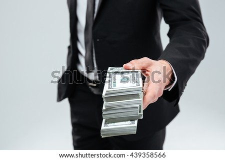 Closeup of businessman in suit and tie giving money to you over white background - stock photo