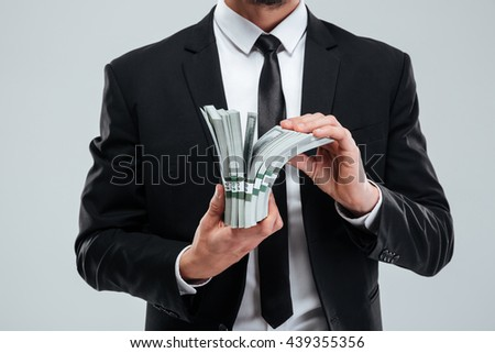 Closeup of businessman in suit and tie holding money over white background - stock photo