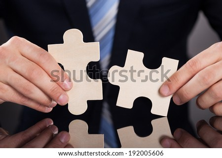 Closeup of businessman joining puzzle pieces at desk