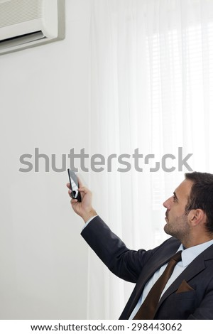 Closeup  of businessman  remote controlling office  temperature with his a smart phone. - stock photo