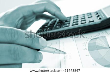Closeup of businessman's hand doing paperwork - blue toned image - stock photo
