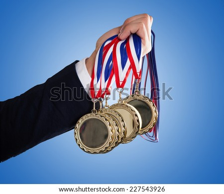 Closeup of businessman's hand holding medals over blue background - stock photo