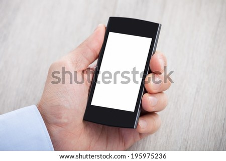 Closeup of businessman's hand holding smartphone with blank screen on desk - stock photo