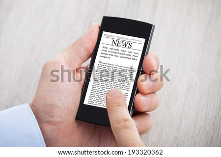 Closeup of businessman's hands surfing news on smartphone at desk - stock photo