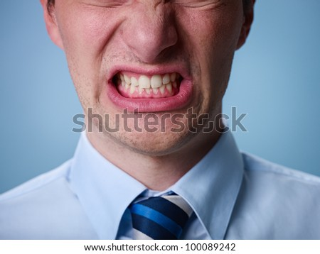 closeup of businessman screaming against blue background. Horizontal shape