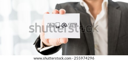 Closeup of businessman showing a white card with contact icons. Conceptual of business information center and support. - stock photo