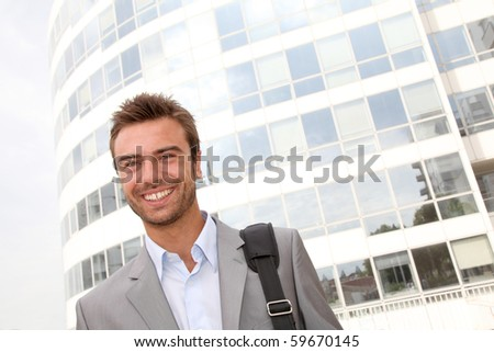 Closeup of businessman standing in front of offices building