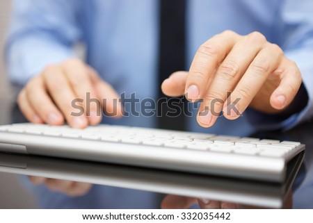 Closeup of businessman typing on modern computer keyboard - stock photo