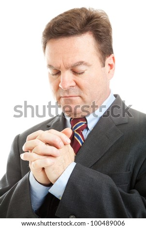 Closeup of businessman with his head bowed in prayer.  White background. - stock photo