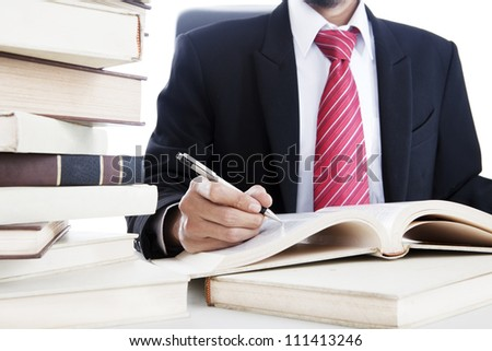 Closeup of businessman writes on a book. shot in the office