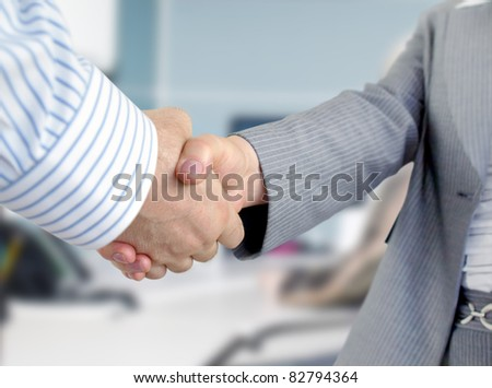 Closeup of businessmen and businesswoman shaking hands. - stock photo