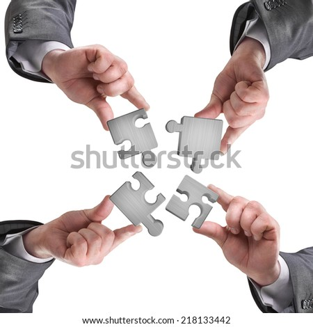 Closeup of businesspeople about to put four puzzle pieces together. isolated on white background - stock photo