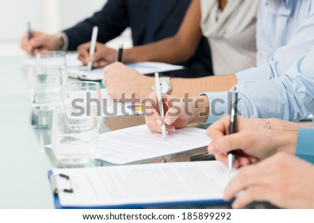 Closeup Of Businesspeople Hand Over Paper Taking Notes At Seminar - stock photo