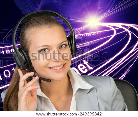 Closeup of businesswoman in headset, her hand on microphone, looking at camera, smiling. Wire-frame building with light as backfrop - stock photo
