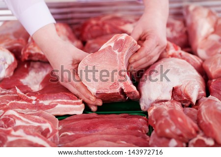 Closeup of butcher's hands holding meat piece in shop - stock photo