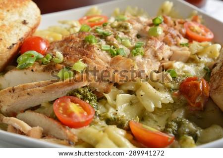 Closeup of cajun chicken on bowtie pasta, closeup, shallow depth of field focus near center - stock photo