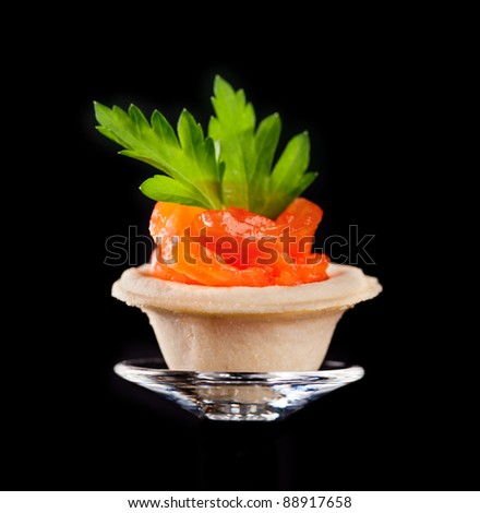 Closeup of canape with smoked salmon fish on glass plate - stock photo
