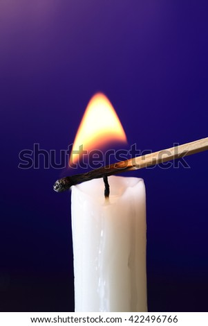 Closeup of candle inflamed with match on dark background - stock photo