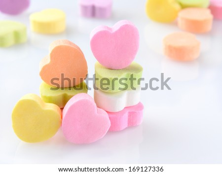 Closeup of candy Valentines hearts on a white reflective surface. Horizontal format with out of focus candies in the background. - stock photo