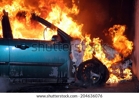 closeup of car burning in the night after a frontal crash collision on the road with flame and smoke - stock photo