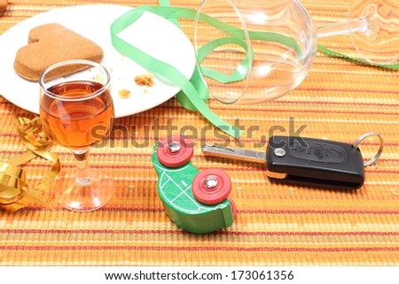 Closeup of car key and overturned model vehicle with glass of wine lying on table after party, car key and alcohol, don't drink and drive concept - stock photo