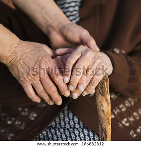 Closeup of caring woman holding female senior's hands - stock photo