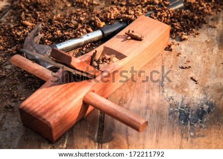 closeup of carpenter plane and hammer on the old wood  - stock photo