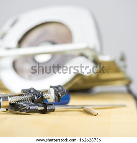 Closeup of carpentry clamps and circular saw in background. - stock photo