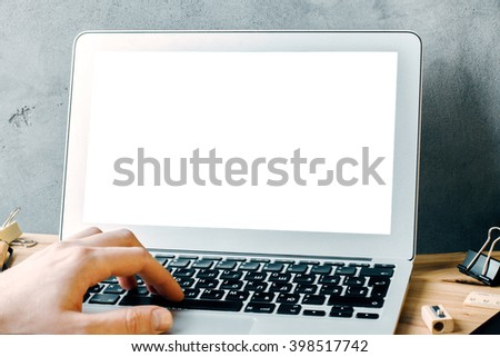 Closeup of caucasian hand typing on laptop with blank white screen. Mock up - stock photo