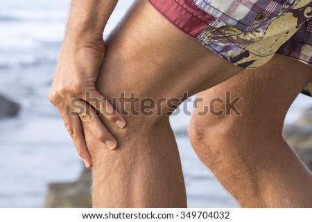 Closeup of Caucasian man's knees wearing shorts at beach while massaging painful sore knee cap - stock photo