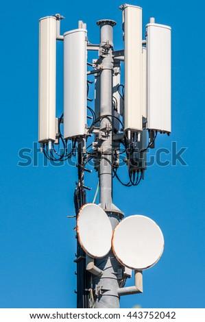 closeup of cellular antenna between trees on blue sky - stock photo