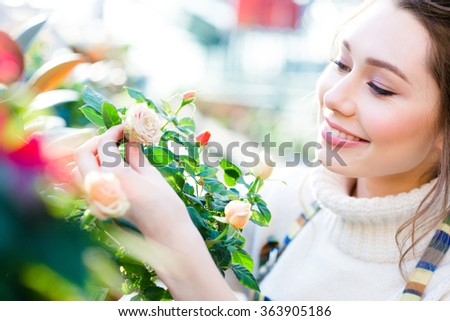 Closeup of charming cheerful woman gardener looking and enjoying roses in garden center - stock photo