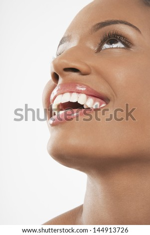 Closeup of cheerful African American woman looking up isolated on white background