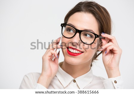 Closeup of cheerful pretty young business woman in glasses talking on cell phone over white background - stock photo