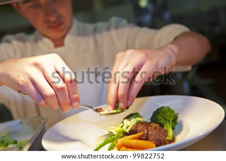 Closeup of chef adding finishing touch on his dish before it goes on the table. - stock photo